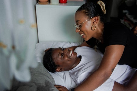 black couple smiling in bed