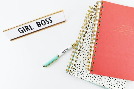 "desk with notebooks and ""girl boss"" plaque on it"