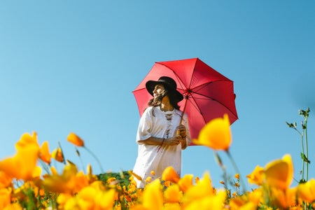 white dress with a red umbrella in a flower field