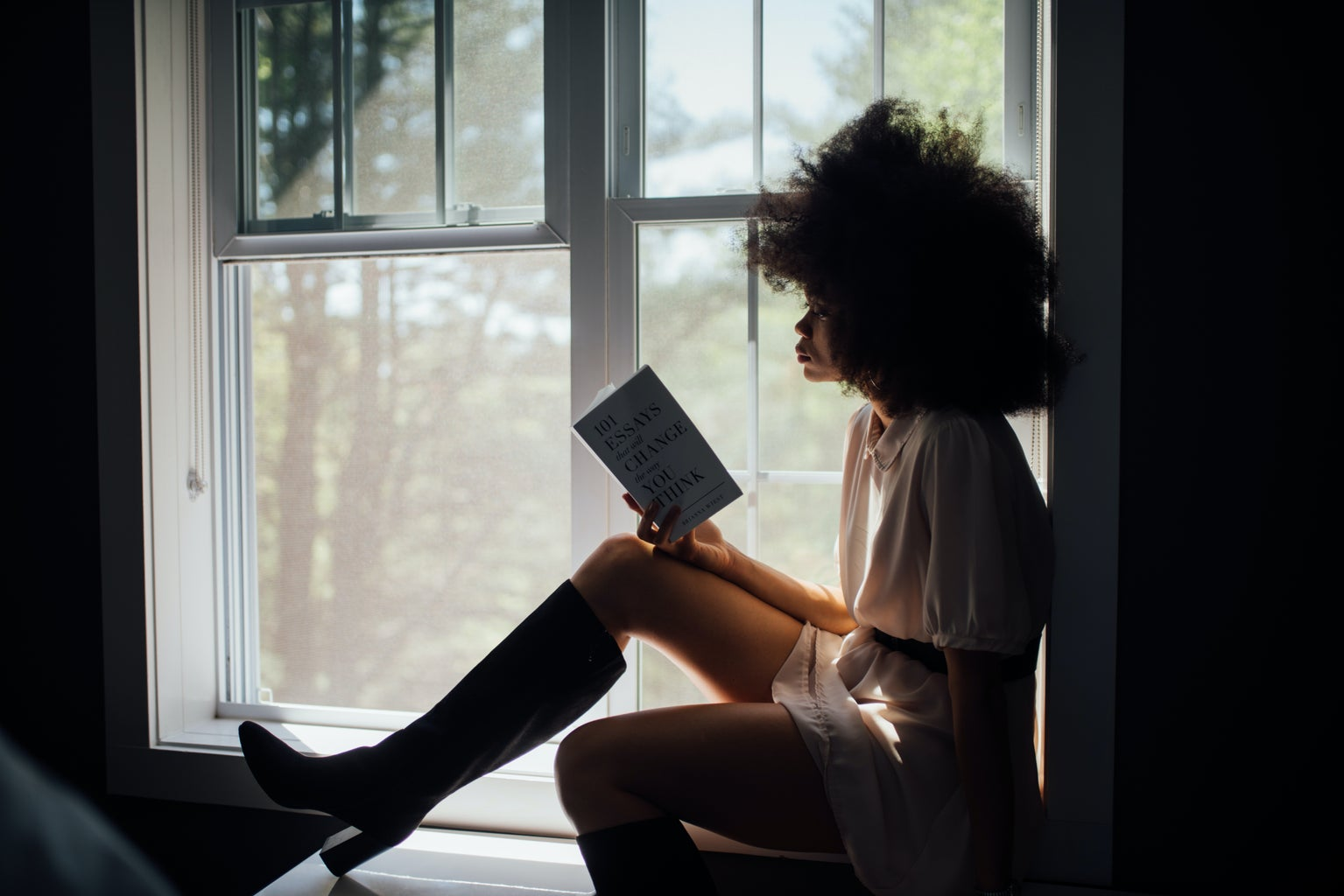 woman sitting at window reading book