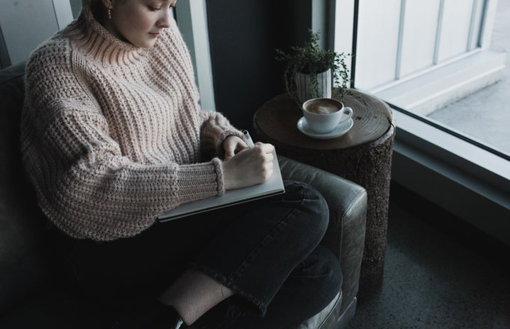 Woman in a light pink sweater sitting beside a window writing in her journal