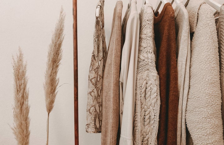 sweaters on clothing rack, sheaf of wheat next to it
