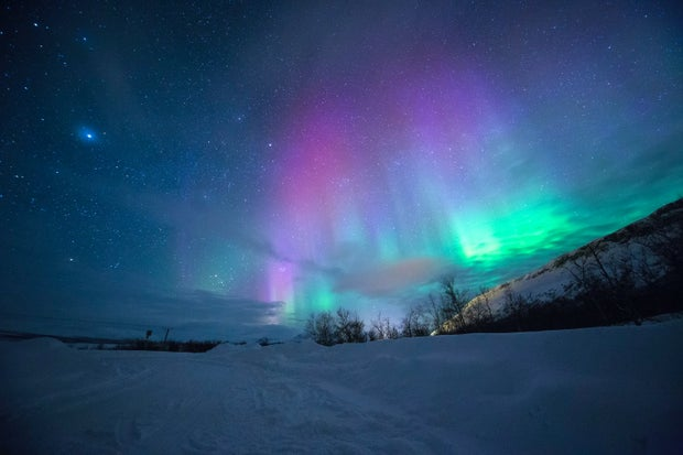 northern lights over snow-capped mountain