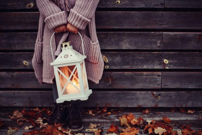 Woman in sweater holding a lantern fall season