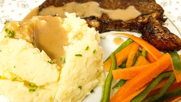 mashed potatoes with gravy, carrots and peppers, and steak on plate