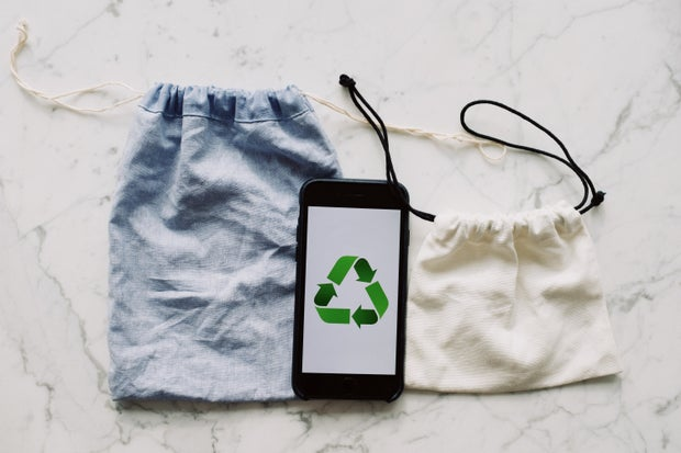 phone with recycling symbols and bags