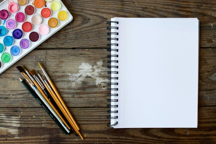 watercolor set with paintbrushes and notebook on wooden table