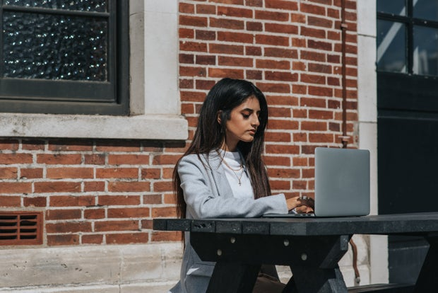 Woman sitting in front of a brick wall at a table with her laptop in front of her.