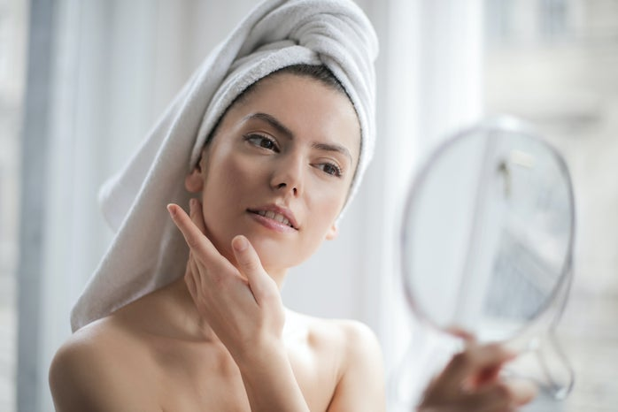 Woman with a towel on head looking in the mirror