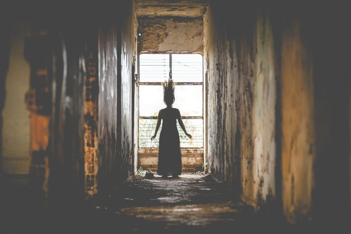 Woman in a dilapidated corridor looking out a window