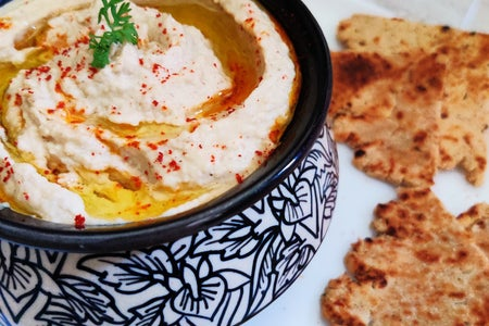 Bowl of hummus with bread around it