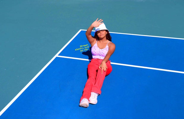 Girl is sitting in a tennis court wearing a white hat and colorful pants. She is holding her hand up to block the sun. The words