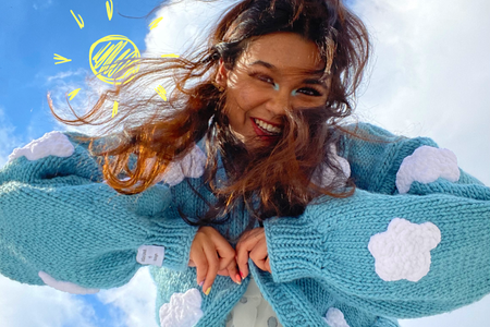 Girl is a white dress and blue sweater with clouds is looking down towards camera smiling. There is an animated/drawn sun in the sky.