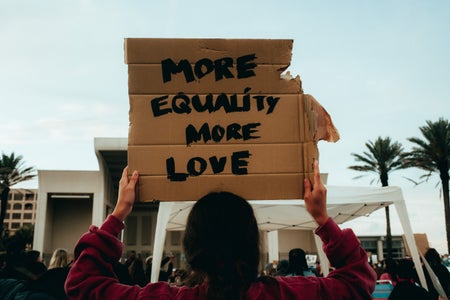 "Person holding cardboard sign saying ""more equality, more love"""