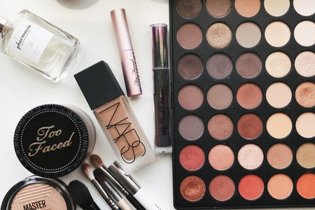 makeup products and candles laying on a table