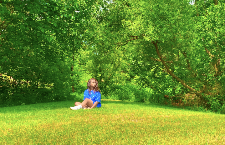 Girl is in a blue outfit, sitting in a field of green grass with trees in the back