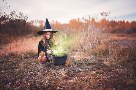 girl in witch's costume in field photoshoot