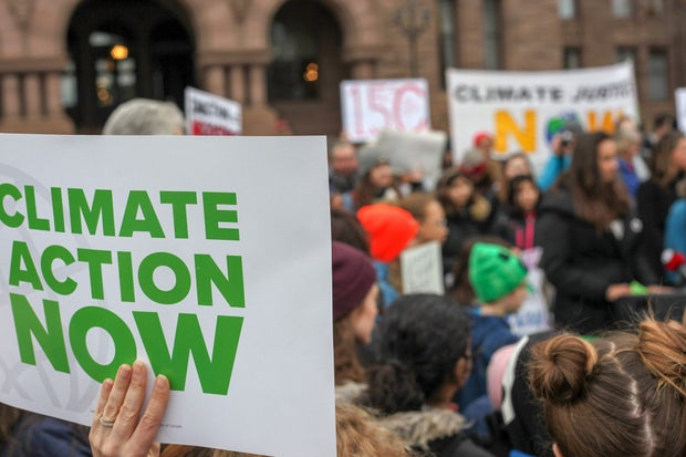 """protest sign that says """"climate action now"""" in front of a crowd"""