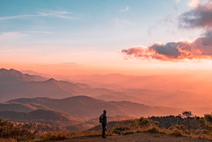 Sunrise, person standing on a mountain top