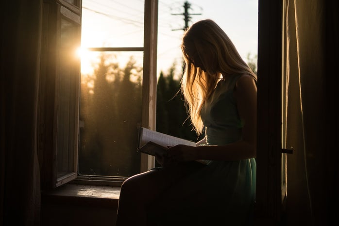 Woman reading on windowsill with sunset in background