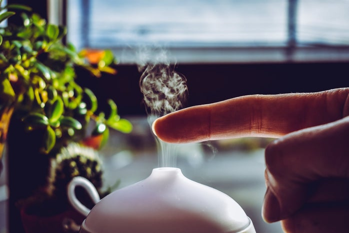 A person putting their finger in the mist from a diffuser.