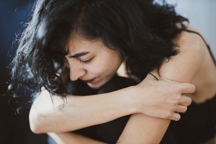 Woman hugging knees.