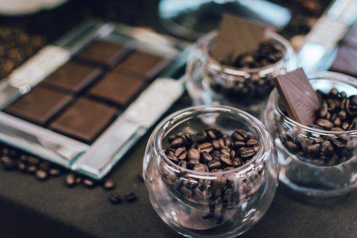Cocoa beans in glass bowls and broken chocolate bars