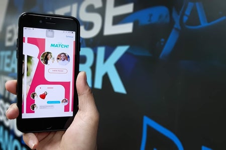 hand holding phone with tinder app on screen