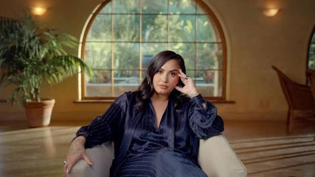 Demi Lovato sitting on a chair with a blue outfit