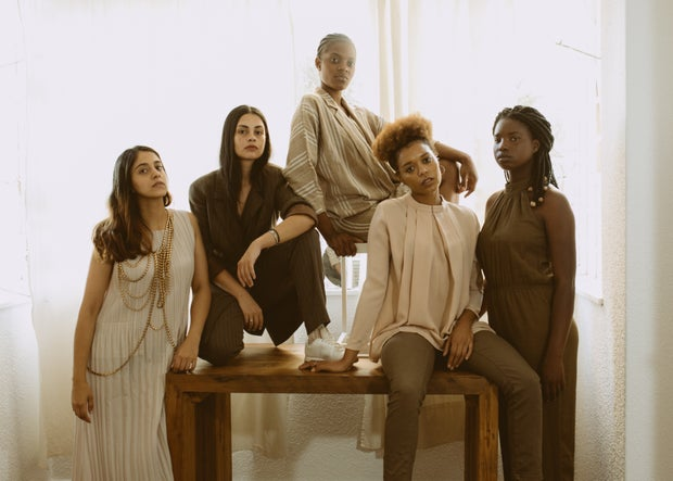 Women sitting on brown wooden bench
