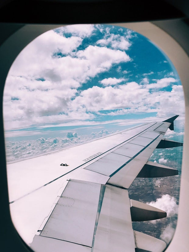 Airplane window wing with clouds