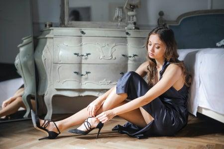 Girl in black dress putting on black heels