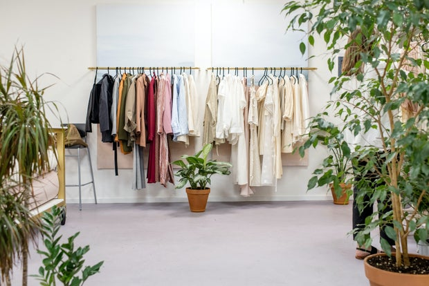 Clothing hangs on a rack with plants on the sides.
