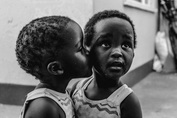 little girl kissing another little girl on the cheek