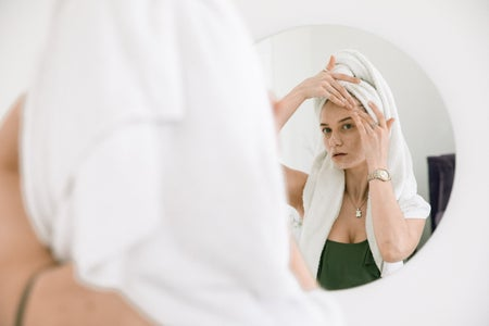 woman standing in front of a mirror applying cream