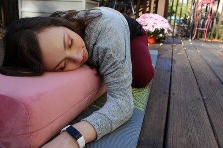 Camryn on a pink yoga bolster in Child's pose