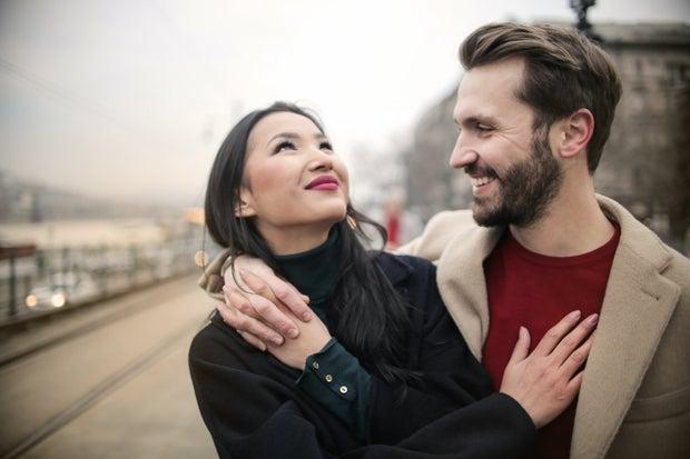 Man in Brown Coat Hugging Woman in Black Coat