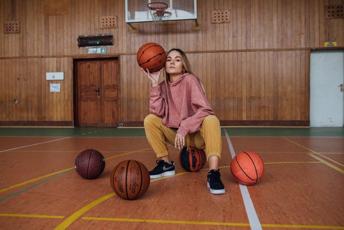 woman sitting and holding a basketball