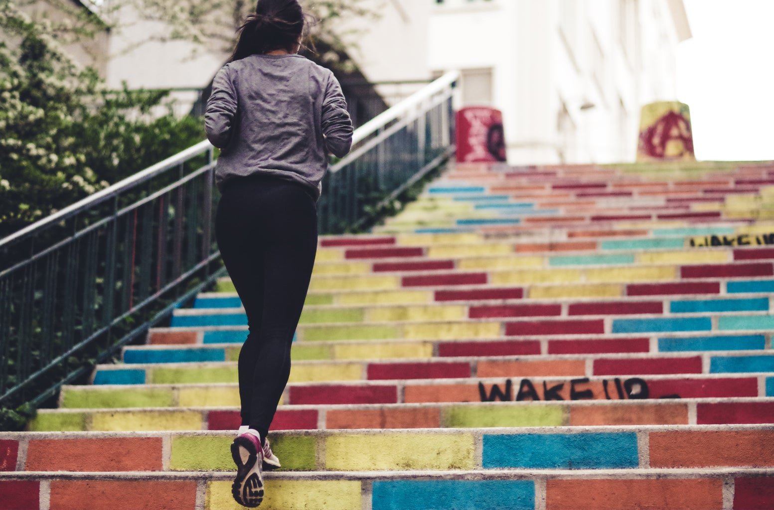 woman running up colorful stairs
