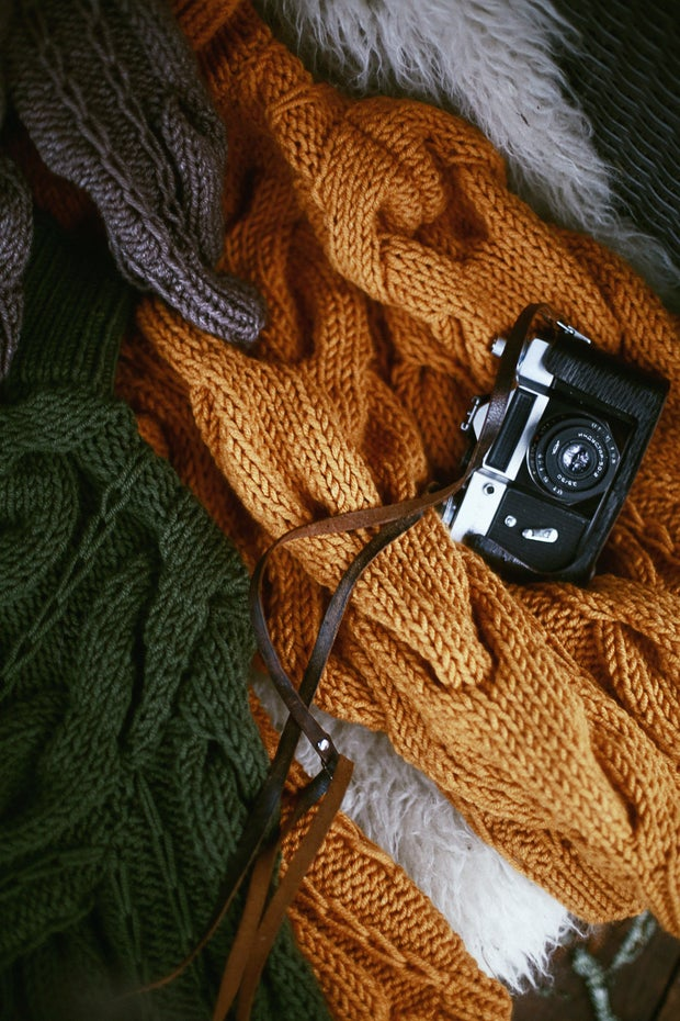 camera laying on top of sweaters
