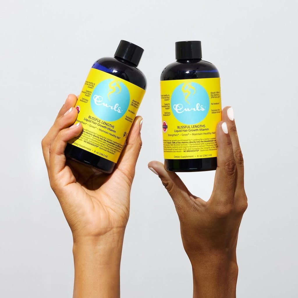Two hands holding up CURLS Blissful Lengths Blueberry Liquid Hair Growth Vitamin