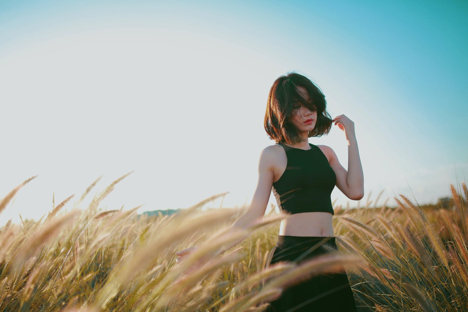 Woman poses in a windy field.