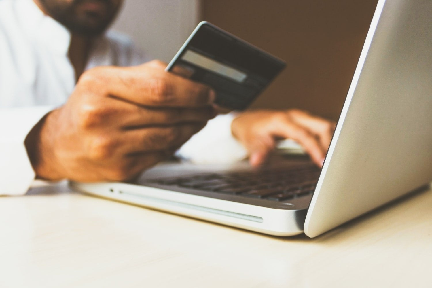Person using laptop holding credit card