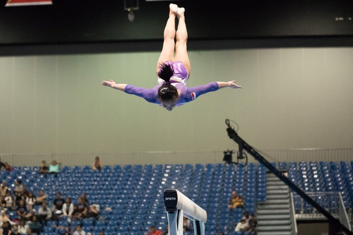 gymnast in a purple leotard performing a mid-air trick over the balance beam