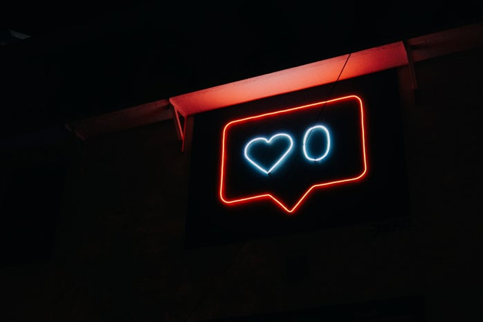 A neon light sign of a notification symbol. The inside contains a blue heart with the number zero next to it.