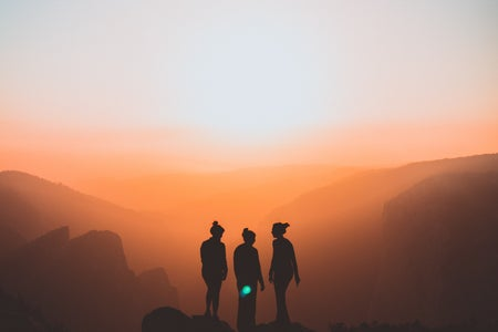silhouette of three people at sunset