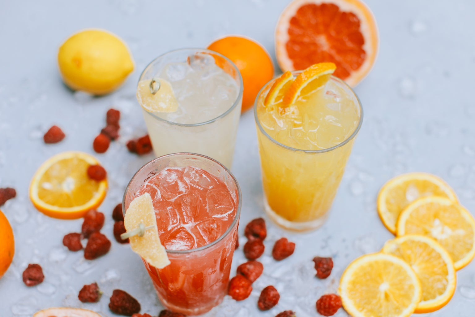 Three glasses of citric cocktails, with grapefruit and lemon