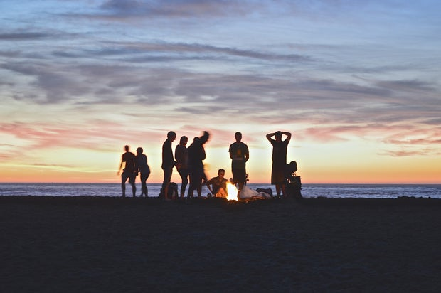 friends by fire on beach