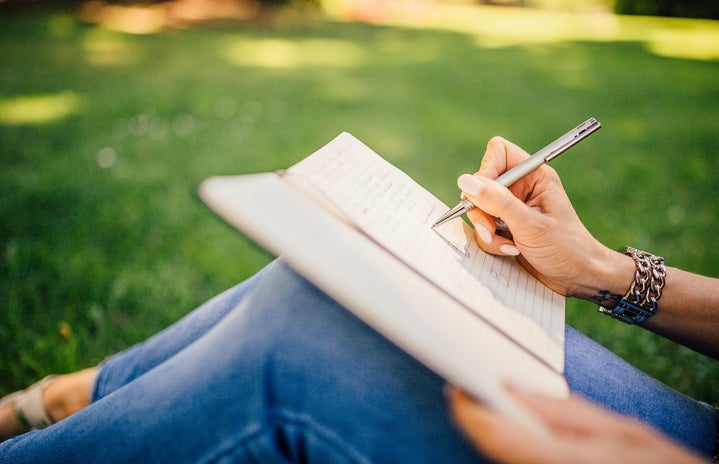 Person sitting on grass writing in journal