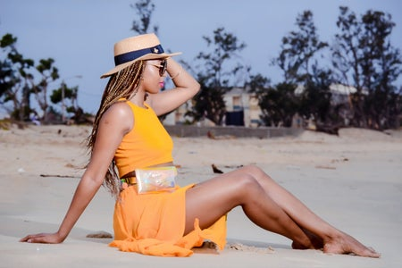 black woman sitting on beach in yellow two piece holding hat